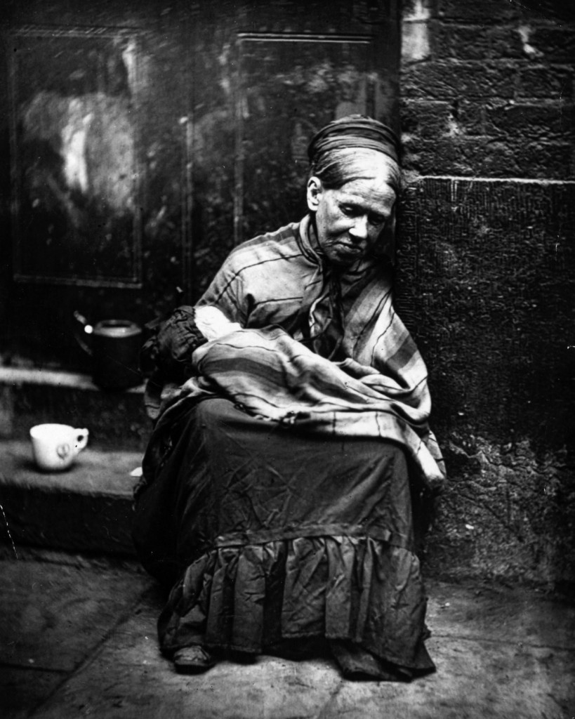 A beggar paid to look after a baby sitting at the side of a street, circa 1877. From 'Street Life in London' by John Thomson and Adolphe Smith - pub. 1877