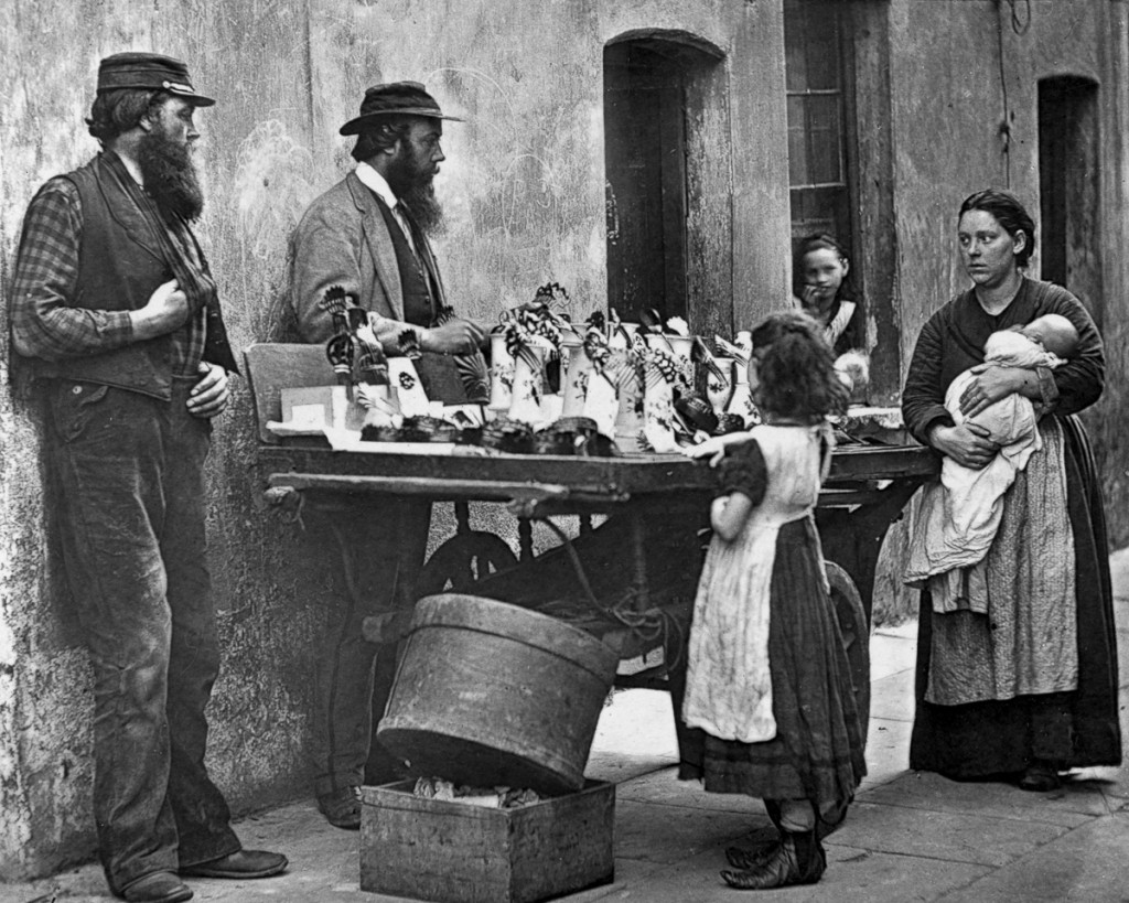 A Victorian fancy wear dealer selling ornaments from his barrow. Original Artwork: From 'Street Life In London' by John Thomson and Adolphe Smith - pub. 1877